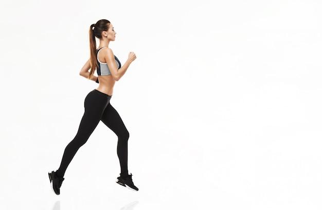 Donna allegra nell'addestramento degli abiti sportivi che funziona sul bianco.