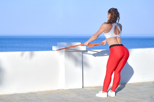 Sportive woman in summer morning training on the beach in red leggings with rubber resistance band, athlete girl workout on sea coast background with fitness elastic