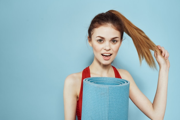 Sportive woman training mat in hands red tank top exercise blue wall.
