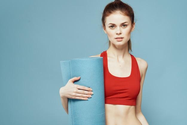 Sportive woman training mat in hands