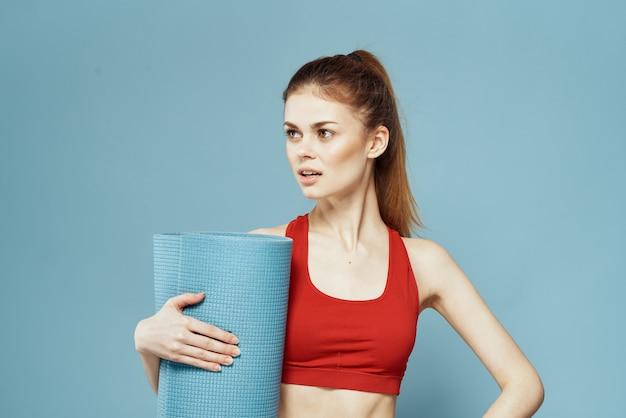 Спортивный коврик тренировки женщины в руке на синем фоне.