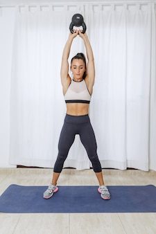 Sportive woman training with kettlebell during workout at home