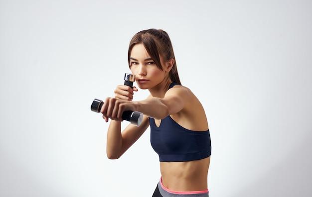Спортивная женщина с гантелями в руках тренирует силовую мотивацию
