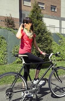 전화로 전화를 걸고 있는 fixie 자전거와 낚시를 좋아하는 여자