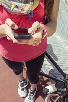 スマートフォンを探しているピストバイクを持つスポーティーな女性
