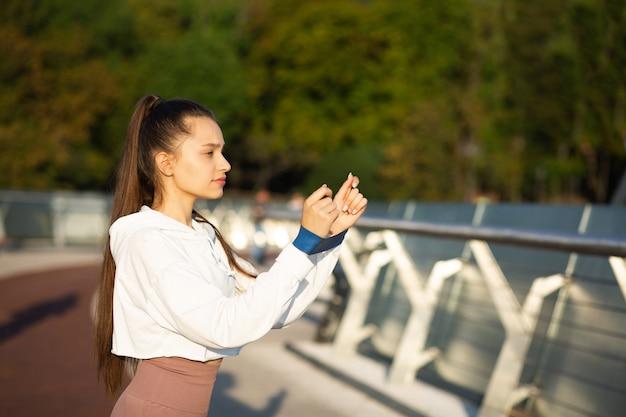 橋でフィットネスバンドで運動する長い髪のスポーティーな女性。コピースペース