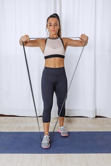 Sportive woman with resistance equipment working out at home