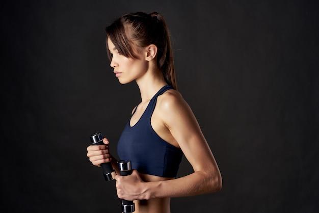 Sportive woman workout motivation slim figure dumbbells in hands dark background