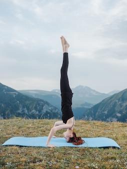 屋外の山でのスポーティーな女性のヨガ瞑想運動