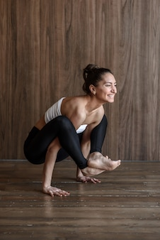 Sportive woman yogi practices yoga in the gym on the floor in a pose