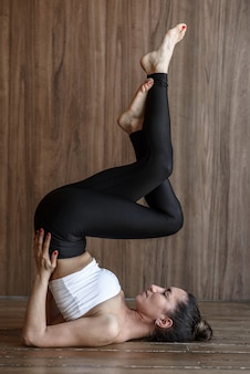 Sportive woman yogi practices yoga in a sports hall on the floor in a pose
