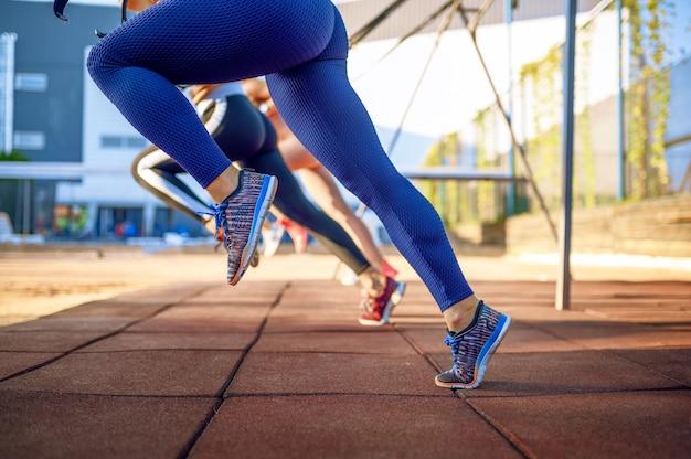 屋外のスポーツグラウンドで運動をしているスポーティーな女性、背面図、屋外でのグループフィットネストレーニング