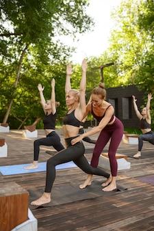 여름 공원에서 강사와 함께 그룹 요가 훈련에 낚시를 좋아하는 여성. 명상, 야외 운동에 맞는 수업