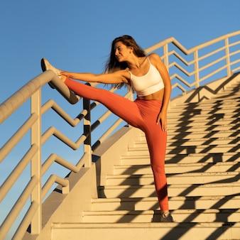 階段で日没時にトレーニングをジョギングした後、ストレッチ運動をしているスポーティーな少女