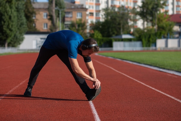 Sportive young man wears headphones doing stretching at the running track. empty space