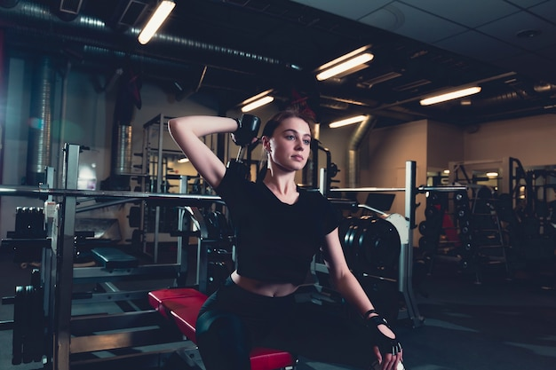Sportive young woman doing exercise with dumbbell in fitness center