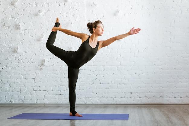 黒のスポーツウェアの白いレンガの壁に対してヨガをしているスポーティーな若い女性は、ヒーの概念...