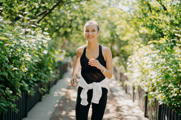 Sportive young woman has jogging workout training runs outdoor smiles pleasantly enjoys good day dressed in sportsclothes listens music from playlist. start day from morning jog. female runner