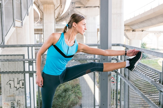 Sportive young woman is stretching before jogging