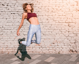 Sportive young woman jumping in air with joy against white brick wall