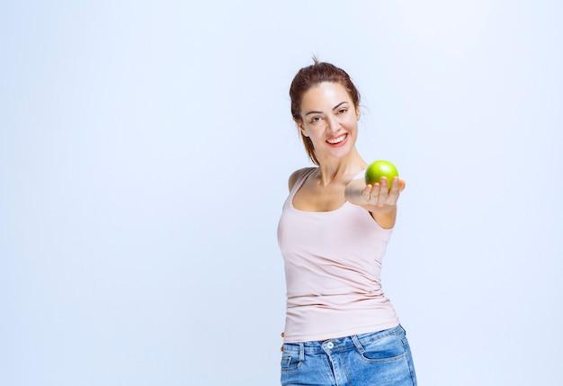 Спортивная молодая женщина, предлагающая зеленые яблоки