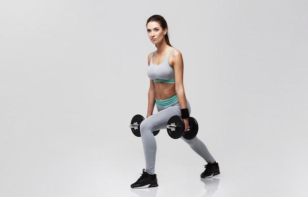 白のダンベルでスクワットを行うトレーニングの陽気な若い女性。