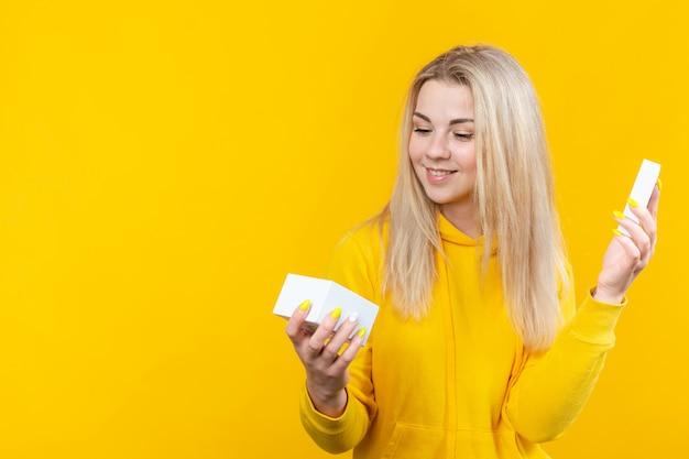 Портрет молодой довольно кавказской белокурой женщины в желтом sportive костюме, раскрывает белую изолированную подарочную коробку ,.