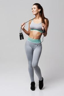 Женщина молодого фитнеса sportive представляя усмехаясь держащ скача веревочку на белизне.