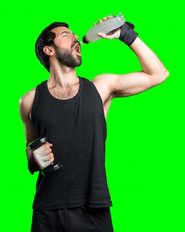 Sportman doing weightlifting drinking water soda