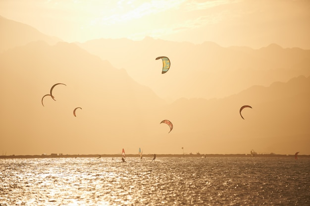 Sportmans kitesurfing on the sea surface against mountains at sunset time