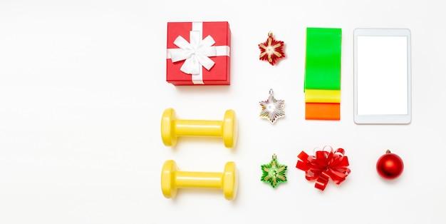 Спортивные аксессуары. гантели, набор резинок, подарочная коробка, планшетный компьютер и рождественские украшения на белом фоне.