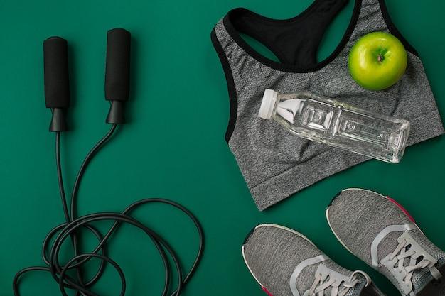 Спортивные аксессуары для фитнеса на зеленом полу концепции здорового образа жизни