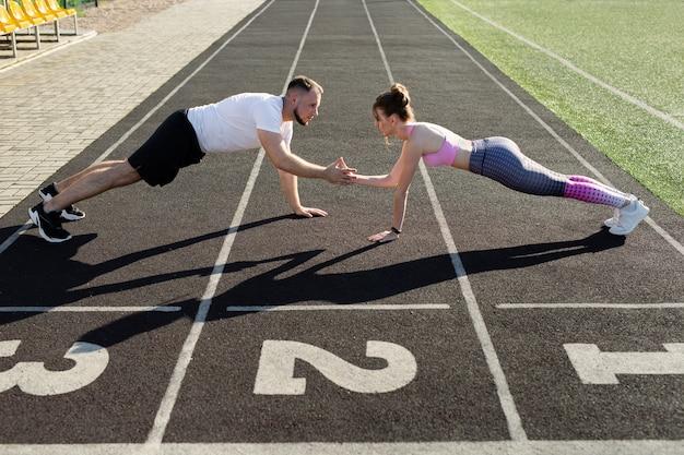 Активные в спорте мужчина и женщина тренируются летом на открытом воздухе на общественном стадионе, стоят на доске и хлопают друг друга по рукам.