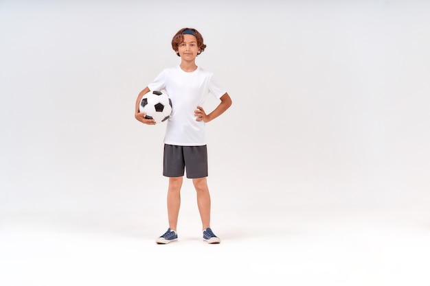 カメラを見てサッカーボールを保持している幸せな10代の少年のスポーツ活動のフルレングスショットと