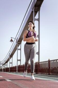 スポーツ活動。橋の上を走りながら笑っているうれしそうなポジティブな女性