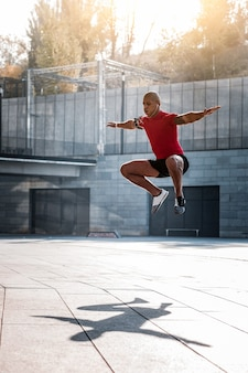 スポーツ活動。スポーツ活動をしながらジャンプするよく構築されたハンサムな若い男