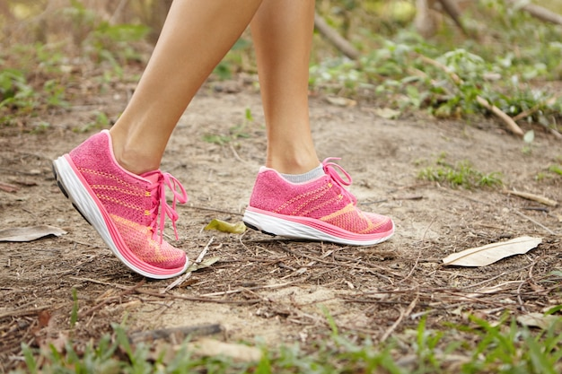 Sports and adventure concept. close up shot of female legs wearing pink running shoes in forest while exercising in summer nature.