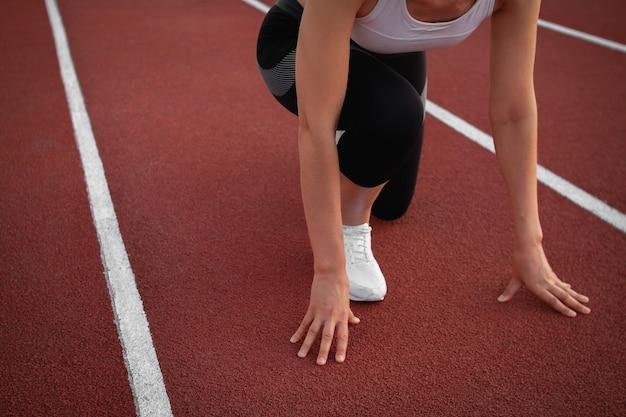 Спорт и фитнес. молодая спортивная женщина в белой футболке и белых кроссовках готовится к бегу на трассе стадиона