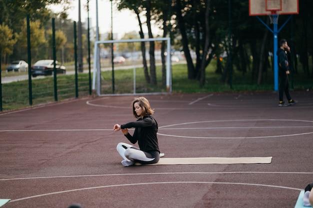 체육관 밖에서 스포츠 및 피트니스. 운동복에 젊은 맞는 여자 야외 운동장에서 열차.