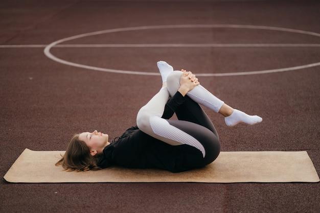 체육관 밖에서 스포츠 및 피트니스. 운동복에 젊은 맞는 여자 야외 놀이터에서 훈련합니다.