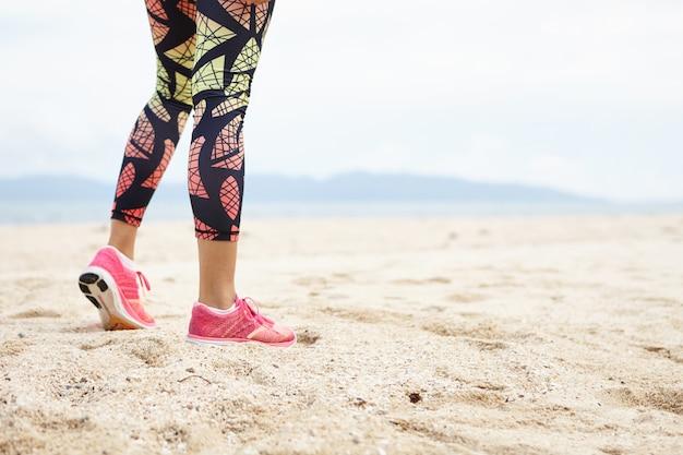 スポーツと健康的なライフスタイルのコンセプト。オーシャンビーチに対して女の子の運動選手の足のショットをトリミングしました。