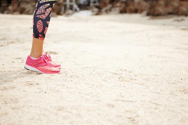 スポーツと健康的なライフスタイルのコンセプト。テキストまたは広告コンテンツのコピースペースとビーチに立っているピンクのランニングシューズの女性ランナーの側面図です。