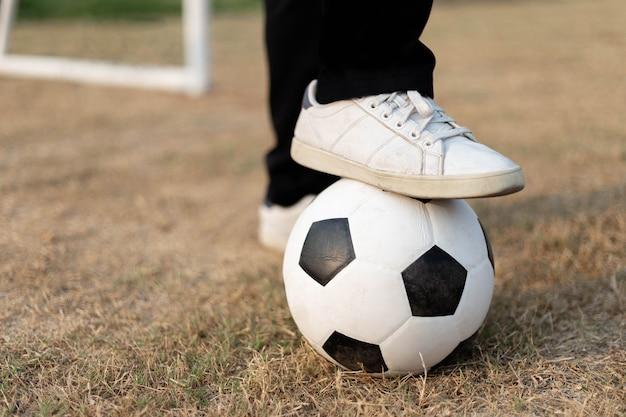 스포츠 및 레크리에이션 축구장에서 흰색 운동화를 신고 발로 공을 멈췄습니다.