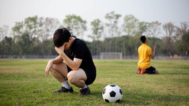 スポーツとレクリエーションは、サッカーの試合後の2人のプレーヤーの勝利と敗北の瞬間です。