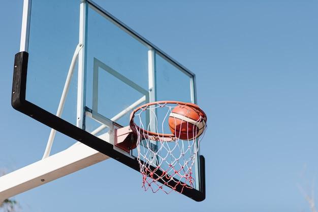 スポーツとレクリエーションのコンセプトは、バスケットボールのフープに向かって空中を流れるバスケットボールのショットです。