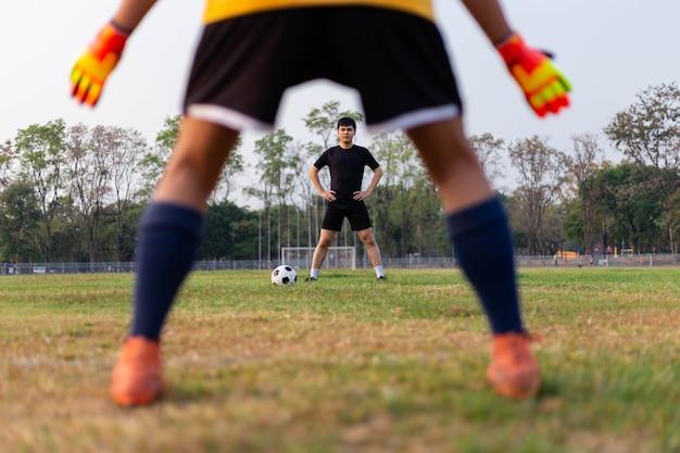 スポーツとレクリエーションのコンセプトは、フリーキックからボールをキャッチするためにゴールキーパーのポジションリハーサルとして練習している男性のアマチュアプレーヤーです。
