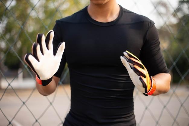 スポーツとレクリエーションの概念は、ボールをキャッチするためにリハーサルを行うゴールキーパーの位置として練習している男性のアマチュアプレーヤーです。