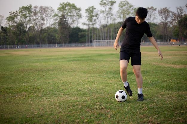 スポーツとレクリエーションのコンセプトは、芝生のフィールドでボールを蹴る練習をしている黒いtシャツとズボンを着た男性のサッカー選手です。