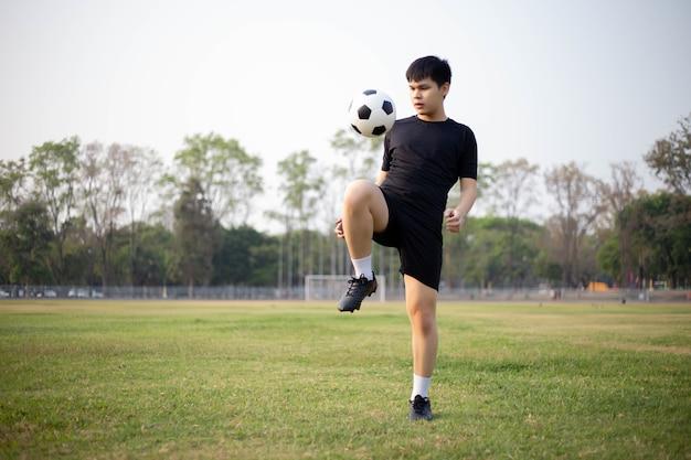 스포츠 및 레크리에이션 개념 검은색 티셔츠와 바지를 입은 남성 축구 선수가 잔디밭에서 공을 차는 연습을 합니다.