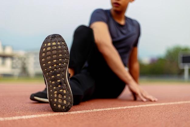 スポーツとレクリエーションのコンセプトは、運動前の準備として体の各部分を伸ばしてウォームアップを行う男性の若者です。